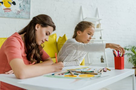 Photo pour Selective focus of attractive babysitter drawing near cute kid in living room - image libre de droit