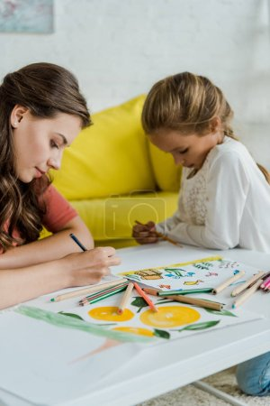 Photo pour Selective focus of babysitter drawing near cute kid in living room - image libre de droit