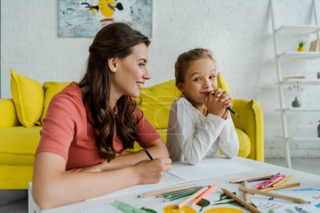 Photo pour Selective focus of cheerful babysitter looking at cute kid in living room - image libre de droit