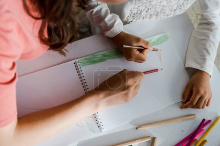 Photo pour Cropped view of babysitter drawing with kid in living room - image libre de droit