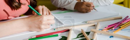 Photo pour Panoramic shot of babysitter drawing with kid in living room - image libre de droit