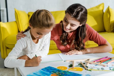 Photo pour Happy babysitter looking at drawing of cute kid - image libre de droit