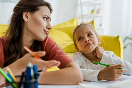 Photo for Selective focus of babysitter showing shrug gesture while looking at kid - Royalty Free Image