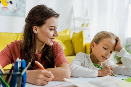 Photo for Selective focus of happy babysitter looking at kid studying in living room - Royalty Free Image