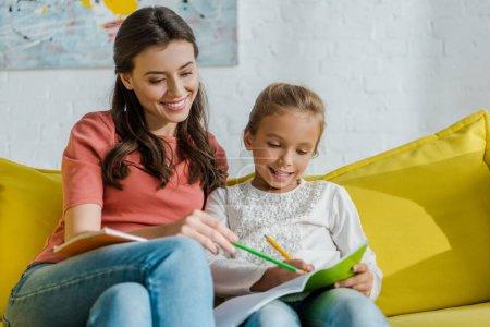 Photo pour Foyer sélectif de baby-sitter heureux avec crayon assis près de l'enfant dans le salon - image libre de droit