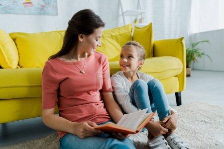 Photo pour Enfant heureux assis sur le tapis près de baby-sitter avec livre - image libre de droit