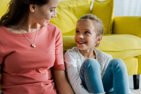 Photo for Happy kid looking at beautiful babysitter at home - Royalty Free Image
