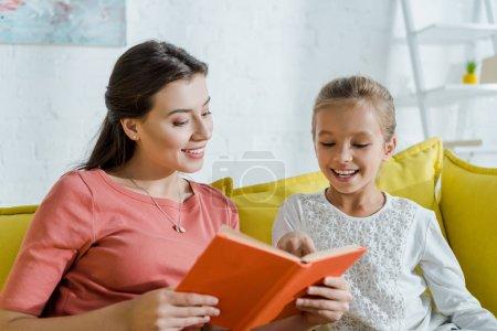 Photo pour Foyer sélectif de l'enfant heureux regardant le livre dans les mains de baby-sitter joyeux - image libre de droit