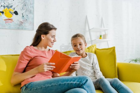 Photo pour Foyer sélectif de l'enfant heureux en regardant le livre dans les mains de baby-sitter souriant - image libre de droit