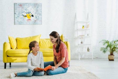 Photo pour Enfant heureux tenant livre tout en étant assis sur le tapis avec baby-sitter - image libre de droit