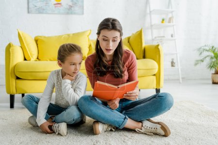 Photo for Cute kid sitting on carpet with babysitter reading book - Royalty Free Image