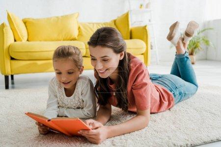 Photo pour Baby-sitter heureux couché sur le tapis avec mignon enfant tout en lisant le livre - image libre de droit