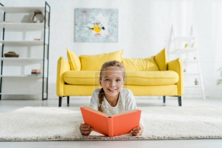 Photo for Happy kid holding book white lying on carpet near yellow sofa - Royalty Free Image