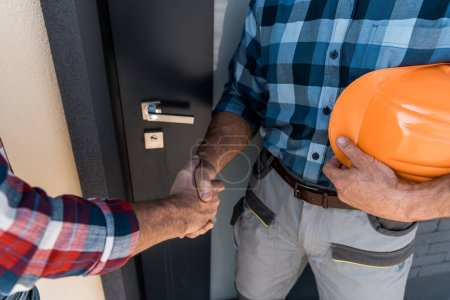 Photo pour Cropped view of builders shaking hands while standing near door - image libre de droit