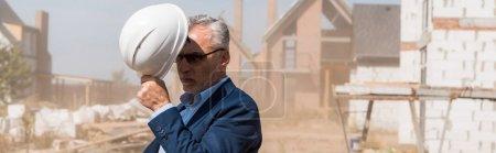 Photo pour Photo panoramique d'un homme d'affaires adulte portant un casque près de bâtiments - image libre de droit