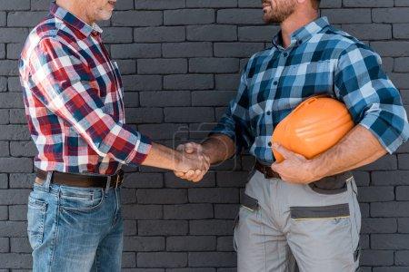 Photo pour Vue recadrée des hommes serrant la main tout en se tenant près du mur de briques - image libre de droit