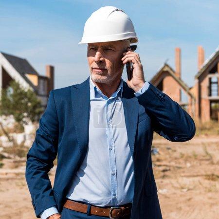 Photo pour Homme d'affaires barbu mature en costume parlant sur smartphone - image libre de droit