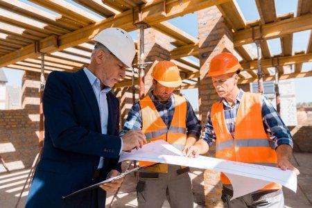Photo pour Homme d'affaires mûr près d'architectes en casques tenant un plan - image libre de droit