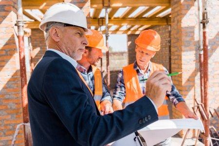Photo pour Homme d'affaires mûr en costume près d'architectes en casques tenant un plan - image libre de droit