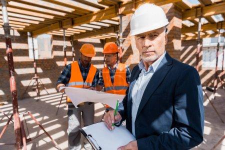 Photo pour Focus sélectif de barbu homme d'affaires mûr avec planche à reliure près des constructeurs - image libre de droit