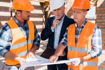 Photo for Mature constructor pointing with finger at blueprint near businessman - Royalty Free Image