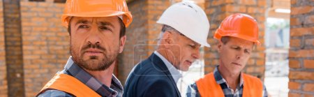 Photo for Panoramic shot of constructor in helmet near coworker and businessman - Royalty Free Image