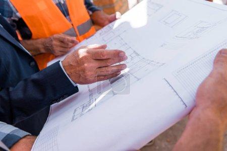 Photo pour Vue recadrée de l'homme d'affaires gestuelle près du plan directeur et des constructeurs - image libre de droit