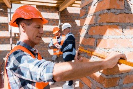 Photo pour Foyer sélectif du constructeur établi mesurant le bâtiment à l'extérieur - image libre de droit