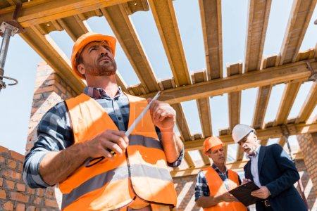 Photo pour Low angle view of handsome bearded builder holding measuring tape - image libre de droit
