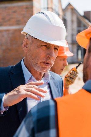 Photo pour Focalisation sélective de l'homme d'affaires mûr dans la gesticulation du casque tout en regardant le constructeur - image libre de droit
