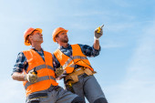 """Постер, картина, фотообои """"low angle view of handsome constructor pointing with finger while standing against blue sky """""""