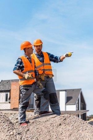 Photo pour Beau constructeur pointant avec un doigt debout sur des pierres près d'un collègue - image libre de droit