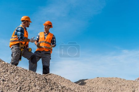 Photo for Selective focus of coworkers in orange helmets standing on stones against sky - Royalty Free Image