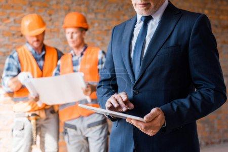 Photo pour Crochet vue d'un homme d'affaires tenant une tablette numérique près de constructeurs - image libre de droit