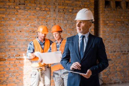 Photo pour Focalisation sélective d'un homme d'affaires mûr tenant une tablette numérique près des constructeurs - image libre de droit