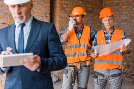 Photo for Selective focus of constructors in helmets near mature businessman holding digital tablet - Royalty Free Image