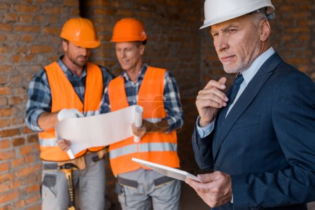 Photo for Selective focus of mature businessman holding digital tablet near architects - Royalty Free Image