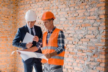 architect holding blueprint near businessman with digital tablet