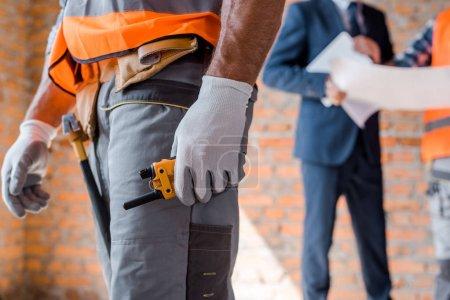 Photo pour Vue recadrée de l'homme tenant talkie walkie près architecte et collègue - image libre de droit