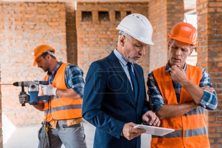 Photo pour Selective focus of businessman and builder looking at digital tablet - image libre de droit
