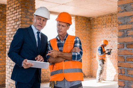 Photo for Selective focus of businessman standing near builder pointing with finger at digital tablet - Royalty Free Image