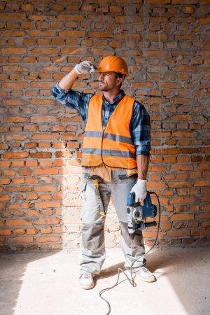 Photo pour Bel homme barbu tenant un marteau perforateur en touchant un casque - image libre de droit