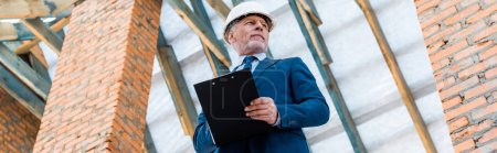 Photo for Panoramic shot of businessman in helmet holding clipboard - Royalty Free Image