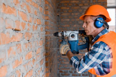 Photo for Mature builder using hammer drill near brick wall - Royalty Free Image