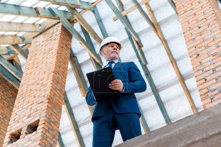 Photo pour Vue à angle bas d'un homme d'affaires portant un casque tenant la planche à pince - image libre de droit