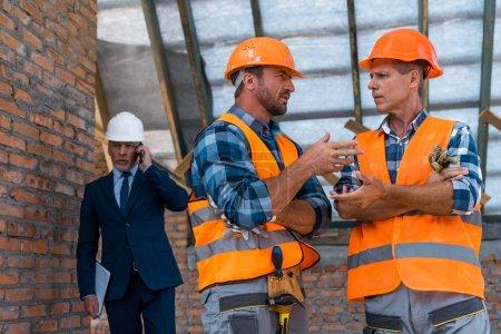 Photo pour Focalisation sélective des constructeurs gesticulation près de l'homme d'affaires parler du smartphone - image libre de droit