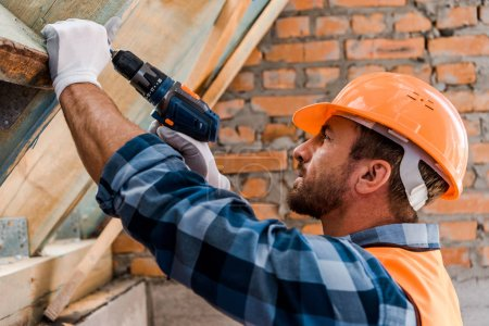 Photo for Side view of handsome constructor in helmet holding hammer drill - Royalty Free Image