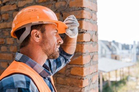 Photo pour Beau constructeur touchant un casque orange - image libre de droit