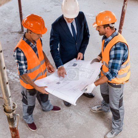 overhead view of builders and businessman holding blueprint