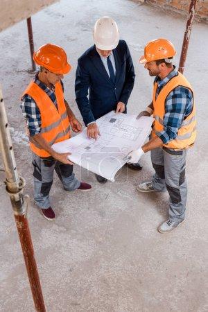 Photo pour Vue aérienne de constructeurs et d'hommes d'affaires tenant un plan - image libre de droit